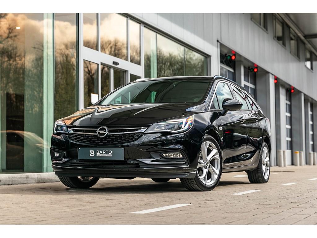 Tweedehands te koop: Opel Astra Zwart - Sports Tourer 14 Turbo 125pk INNOVATNavialu velgen